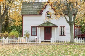 Quaint small home with white picket fence