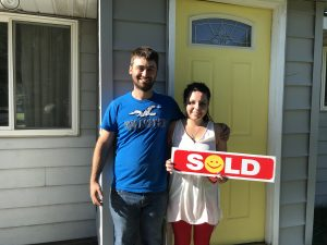 First time homebuyers holding a sold sign