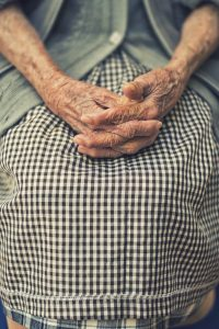 Older woman with hands clasped in her lap