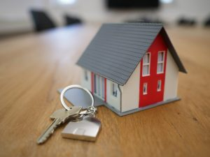 Toy home next to house keys representing a sold home
