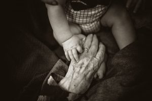 Two hands touching one is a baby the other is an older person's hand
